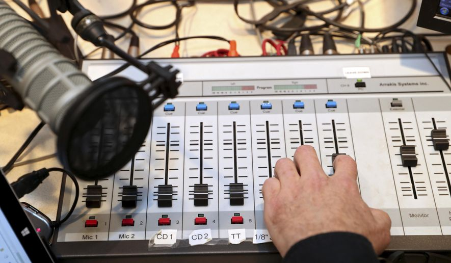 """ADVANCE FOR USE SUNDAY, MARCH 12 - In this Feb. 22, 2017 photo Russell Perry works sound mixing board at WTJU in Charlottesville, Va. WTJU 91.1 FM recently aired a two-hour introduction to its series """"Jazz at 100."""" (Ryan M. Kelly/The Daily Progress via AP)"""