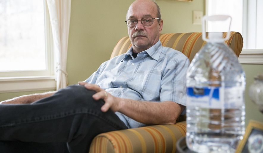 In a March 1, 2017 photo, Dan Marrow poses with a bottle of water in his home in Dumfries, Va. Marrow lives near the Dominion Possum Point Power Station and stopped using his well water over a year ago because he believes it is heavily contaminated and has contributed to health problems he and his family have experienced for years. (Mike Morones/The Free Lance-Star via AP)