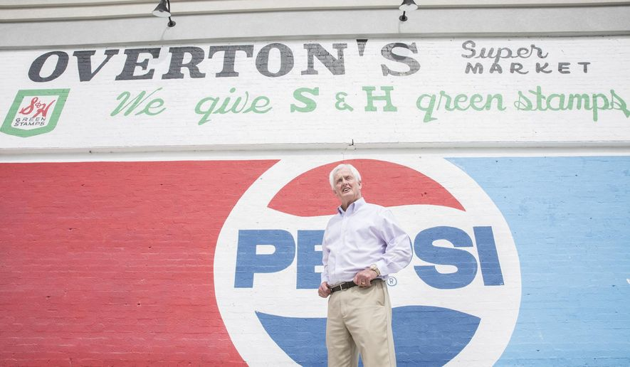 ADVANCE FOR RELEASE SATURDAY, MARCH 11, 2017, AT 12:01 A.M. EST - In this Feb. 22, 2017, photo, Parker Overton stands in front of a mural advertising Overton's, a grocery store he once owned in Greenville, N.C. (Joe Pellegrino/The Daily Reflector via AP)