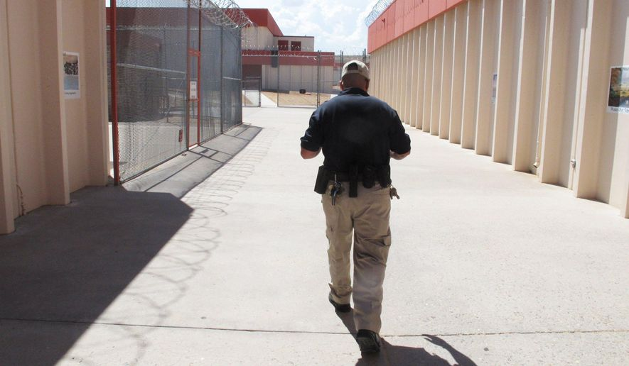 FILE - This Aug. 6, 2012 file photo shows Corrections Officer Xavier Hernandez, a U.S. Army veteran who served in Iraq and Afghanistan, walks through the Central New Mexico Corrections Facility in Los Lunas, N.M. New Mexico Gov. Susana Martinez has directed the state's correction department to work with federal authorities on checking inmates' immigration statuses. The governor's office said Friday, March 10, 2017, the Trump Administration asked the state for permission to interview prisoners who were born in foreign countries. (AP Photo/Russell Contreras,File)