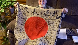 This Nov. 11, 2016 photo shows Marvin Strombo of Dixon, Mont. holds a flag that he took from a Japanese officer who died during the Battle of Saipan in 1944. He hopes it will be returned to the family of the soldier. A University of Montana assistant professor identified the soldier as Yasue Sadao.  ( Kira Veracruyssen/Missoulian via AP)