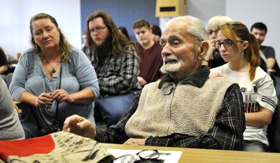 This Nov. 21, 2016 photo shows World War II veteran Marvin Strombo, right, talks to a Japanese Culture and Civilization class at the University of Montana in Missoula, Mont., about his experiences as a young Marine fighting in the Pacific during World War II. Strombo, 93, also brought a Japanese flag, on the desk in front of him, that he took from a slain Japanese officer in the Battle of Sapian that he's hoping can be returned to the man's family.   (Tom Bauer/The Missoulian via AP)