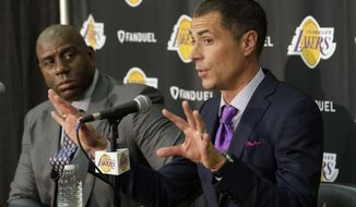 Magic Johnson, left, listens as Rob Pelinka talks during a news conference introducing him as the new general manager for the Los Angeles Lakers, in El Segundo, Calif., Friday, March 10, 2017. The Lakers introduced Pelinka, Kobe Bryant's longtime agent, as their new general manager. Pelinka will work with Johnson to rebuild the 16-time NBA champions from the worst four-year stretch in team history. (AP Photo/Nick Ut)