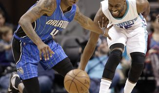 Charlotte Hornets' Kemba Walker, right, and Orlando Magic's Elfrid Payton (4) chase a loose ball in the first half of an NBA basketball game in Charlotte, N.C., Friday, March 10, 2017. (AP Photo/Chuck Burton)