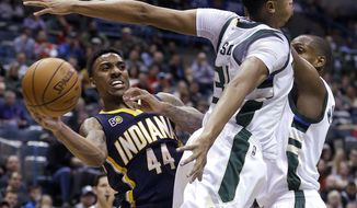 Indiana Pacers' Jeff Teague (44) passes around Milwaukee Bucks' John Henson, middle, and Khris Middleton, right, during the first half of an NBA basketball game Friday, March 10, 2017, in Milwaukee. (AP Photo/Aaron Gash)