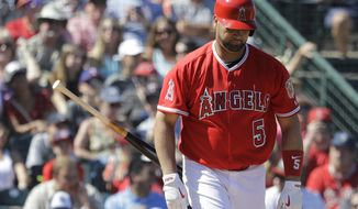 Los Angeles Angels' Albert Pujols tosses his bat after walking during the third inning of a spring training baseball game against the Los Angeles Angels, Friday, March 10, 2017, in Tempe, Ariz. (AP Photo/Darron Cummings)