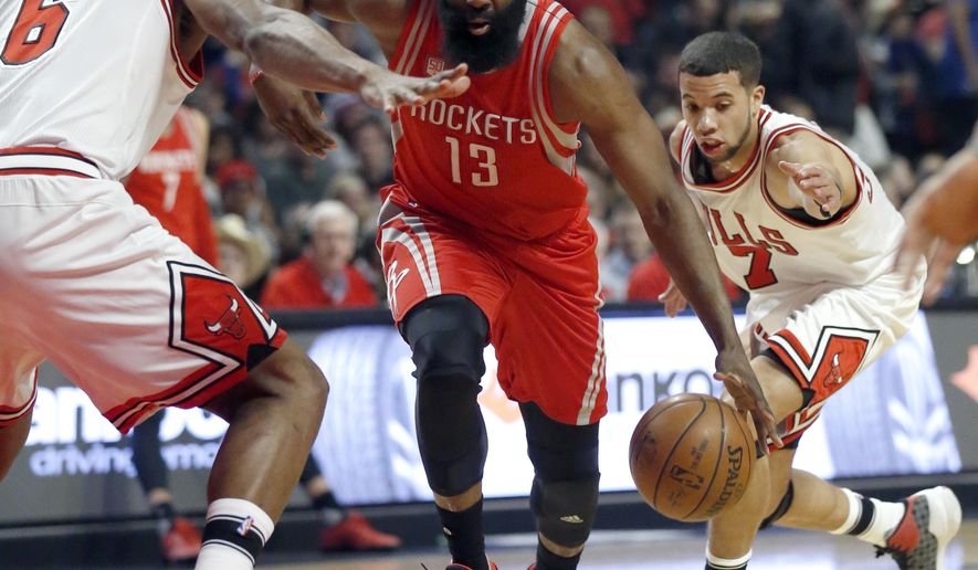 Houston Rockets guard James Harden (13) drives between Chicago Bulls forward Cristiano Felicio, left, and guard Michael Carter-Williams during the first half of an NBA basketball game Friday, March 10, 2017, in Chicago. (AP Photo/Nam Y. Huh)