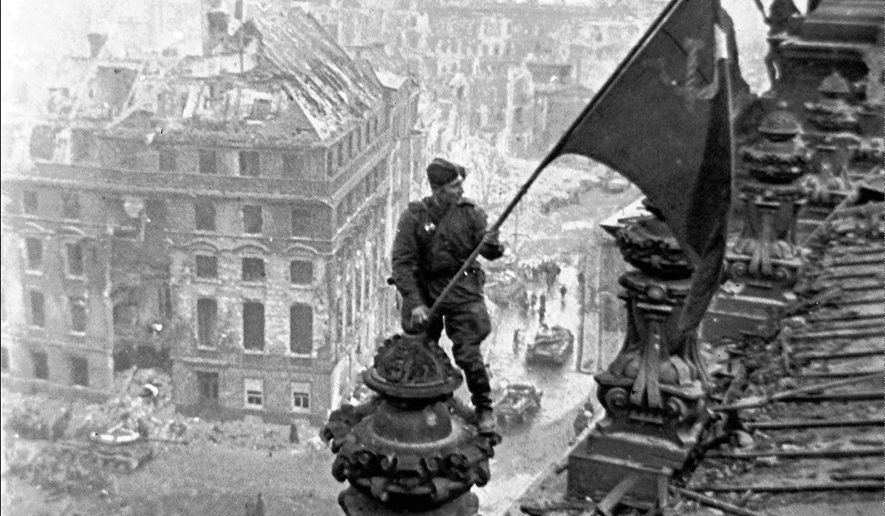 FILE- In this May 2, 1945 file photo, Soviet soldiers hoist the red flag over the Reichstag after the fall of Berlin, which is one of the iconic images of World War II taken by renowned photographer Yevgeny Khaldei.  Just days before the 100th anniversary of Yevgeni Khaldei's birth, the daughter of the photographer who took the iconic WWII image of Red Army soldiers atop the Reichstag, Anna Khaldei has regained possession of his original negatives after a 15-year court battle and is now hoping to mount an exhibition of her father's work, recording history through his lens. (Yevgeny Khaldei/iTAR-TASS file photo via AP)