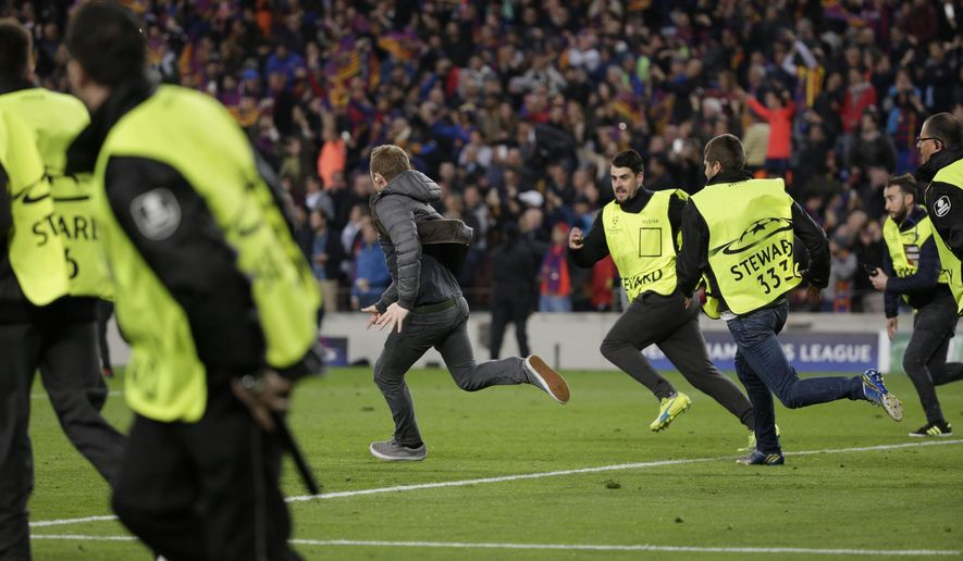 A pitch invader runs followed by stewards at the end of the Champions League round of 16, second leg soccer match between FC Barcelona and Paris Saint Germain at the Camp Nou stadium in Barcelona, Spain, Wednesday March 8, 2017. Barcelona won 6-1. (AP Photo/Emilio Morenatti)
