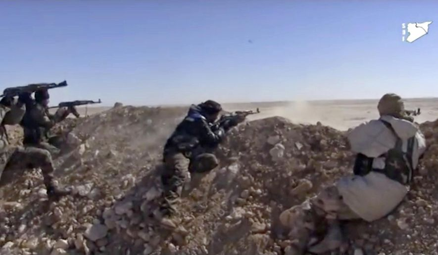 FILE - This frame grab from a video provided by the Syria Democratic Forces (SDF), shows fighters from the SDF opening fire on an Islamic State group's position, in Raqqa's eastern countryside, Syria, Monday, March 6, 2017. The main U.S.-backed force fighting the Islamic State group in Syria has enough fighters to capture the extremists' de facto capital of Raqqa north of the country at a time when U.S. troops are playing a bigger role on the ground in the battle to conquer the city, a spokeswoman for the force said Friday, March 10, 2017. (Syria Democratic Forces, via AP)