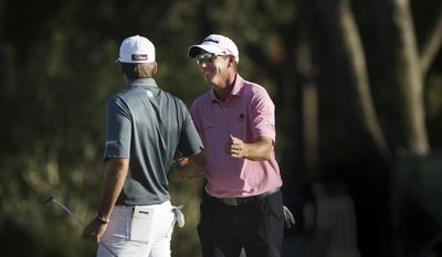 Jim Herman, right, congratulates Ben Martin at the end of their second round while competing in the Valspar Golf Championship at Innisbrook Resort and Golf Club's Copperhead Course on Friday, March 10, 2017, in Palm Harbor, Fla. (Douglas R. Clifford/The Tampa Bay Times via AP)