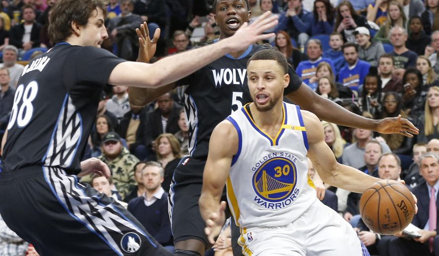 Golden State Warriors' Stephen Curry, front right, works between Minnesota Timberwolves' Nemanja Bjelica, left, of Serbia, and Gorgui Dieng, of Senegal, during the second half of an NBA basketball game Friday, March 10, 2017, in Minneapolis. (AP Photo/Jim Mone)