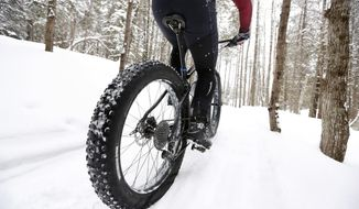"In this Saturday, Feb. 11, 2017 photo a fat tire bicyclist rides on a cross country ski trail during a race at the Sugarloaf ski resort in Carrabassett Valley, Maine. Gone are the days when cyclists had to hang up their bikes the winter. These days, many of them are grinding through winter's snow and spring's mud thanks to trendy new ""fat bikes"" with extra wide tires. (AP Photo/Robert F. Bukaty)"