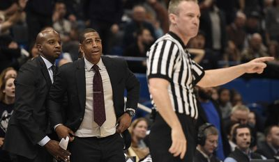 Connecticut head coach Kevin Ollie, center, reacts to a call by official Ron Groover as assistant coach Dwayne Killings, left, looks on, during the second half of an NCAA college basketball game in the American Athletic Conference tournament semifinals, Saturday, March 11, 2017, in Hartford, Conn. (AP Photo/Jessica Hill)