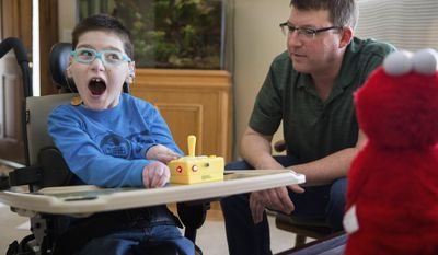 Evan Miller, who has quad spastic paresis, laughs as he plays with toys modified for his abilities with his father Aaron Miller at their home Sunday, Feb 26, 2017, in Omaha, Neb. (Rebecca Gratz/The World-Herald via AP)