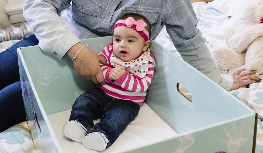 Dolores Peterson and her three-month-old daughter Ariabella pose for a photograph at their home in Camden, N.J., Monday, March 6, 2017. New Jersey became the first state to send newborn babies and their parents home with a box that doubles as a crib and full of necessities, with the aim of cutting back on sudden infant death syndrome. (AP Photo/Matt Rourke)