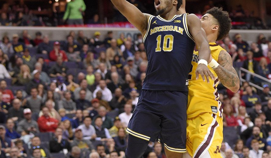 Michigan guard Derrick Walton Jr. (10) goes to the basket against Minnesota guard Nate Mason, right, during the first half of an NCAA college basketball game in the Big Ten tournament, Saturday, March 11, 2017, in Washington. (AP Photo/Nick Wass)