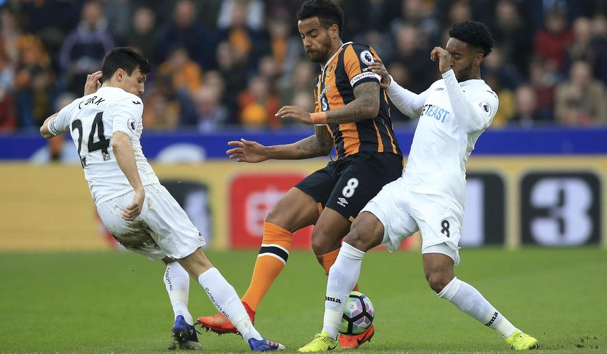 Hull City's Tom Huddlestone, centre, in action with Swansea City's Jack Cork, left, and Leroy Fer, during their English Premier League soccer match at the KCOM Stadium in Hull, England, Saturday March 11, 2017. (Nigel French/PA via AP)