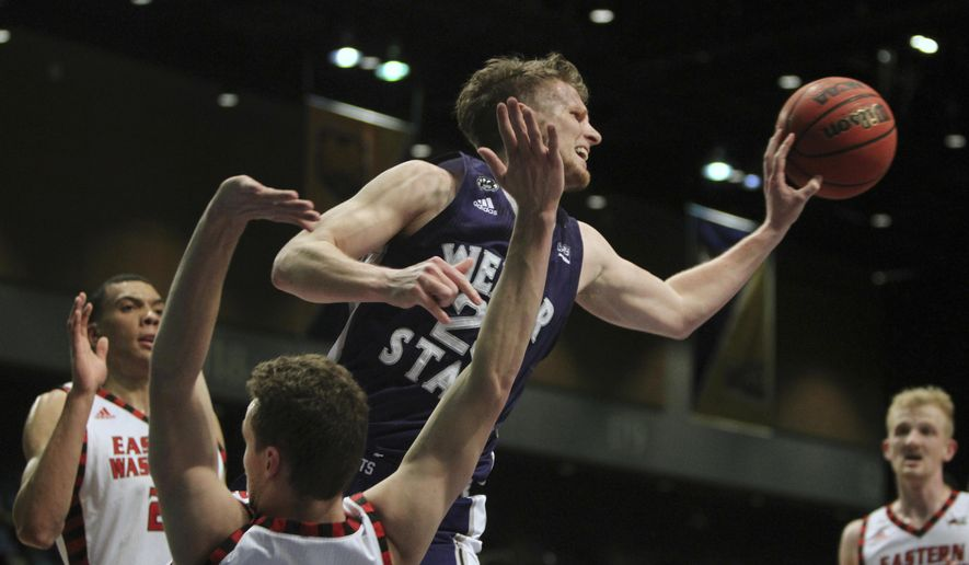 Weber State guard Dusty Baker (25) passes off under the basket between Eastern Washington defenders during the first half an NCAA college basketball game in the semifinals of the Big Sky tournament in Reno, Nev., Friday, March 10, 2017. (AP Photo/Lance Iversen)