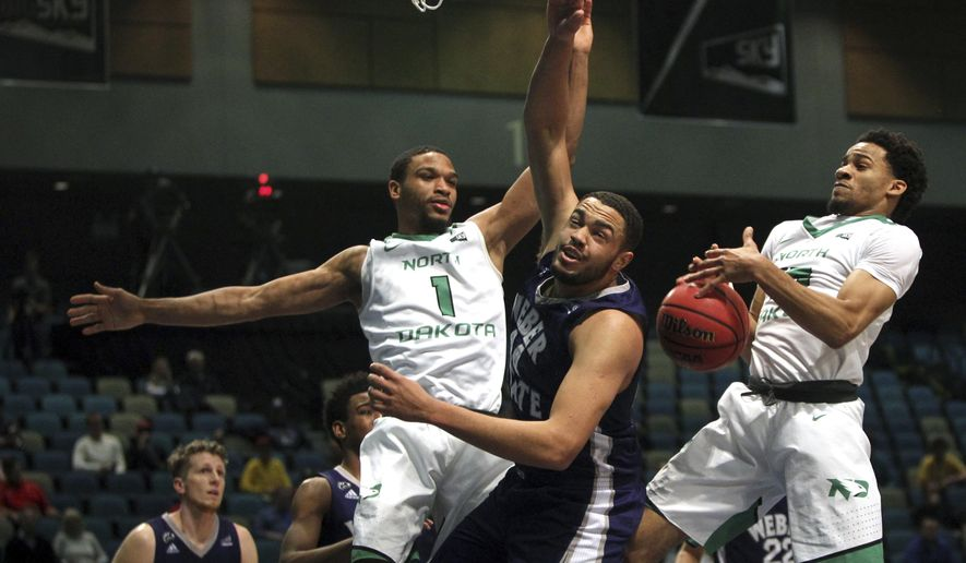 North Dakota guard Corey Baldwin (1) and guard Cortez Seales (15) battle Weber State center Zach Braxton (44) for a rebound during the first half in an NCAA college basketball game in the finals of the Big Sky tournament in Reno. Nev., Saturday, March 11, 2017. (AP Photo/Lance Iversen)