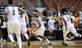 UC Davis' Chima Moneke, center, celebrates his game-winning basket to defeat Cal State Fullerton in an NCAA college basketball game at the Big West men's tournament Friday, March 10, 2017, in Anaheim, Calif. UC Davis won 66-64 in overtime. (AP Photo/Jae C. Hong)