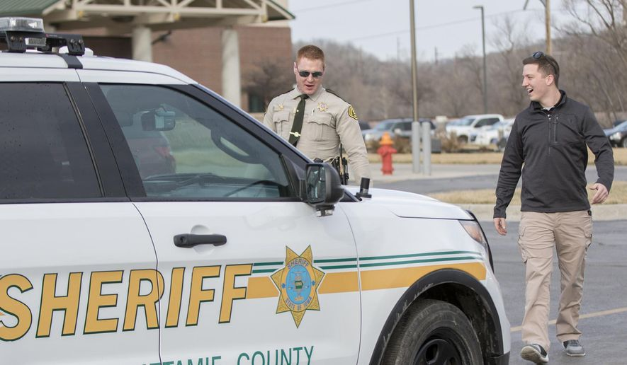 ADVANCE FOR USE SATURDAY, MARCH 11 - In this Friday, March 3, 2017 photo, Noah Hahn, right, a 19-year-old Lewis Central graduate and current junior at the University of Nebraska at Omaha majoring in criminal justice, prepares to ride along on a road patrol with Sheriff's Deputy Eric Shea in Council Bluffs, Iowa. Hoping to follow a career in law enforcement, Hahn is participating in an internship program through the Pottawattamie County Sheriff's Office. (Joe Shearer/The Daily Nonpareil via AP)