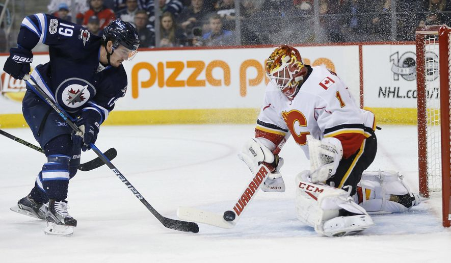 Calgary Flames goalie Brian Elliott (1) knocks the puck away from Winnipeg Jets' Nic Petan (19) during second period NHL hockey action in Winnipeg, Manitoba, Saturday, March 11, 2017. (John Woods/The Canadian Press via AP)