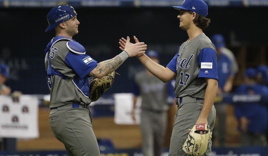 FILE - In this March 7, 2017 file photo, Israel's pitcher Dean Kremer, right, celebrates his team's victory with catcher Nick Rickles against Taiwan after the first round game of the World Baseball Classic at Gocheok Sky Dome in Seoul, South Korea.  Team Israel is tearing up the World Baseball Classic, upsetting a trio of top 10 teams and generating a buzz with their plucky play, colorful fans and unusual mascot. But back in their supposed homeland, no one seems to be taking notice in a country where the game has long been overlooked as arcane and boring. The current team, made up almost entirely of American pros of Jewish descent, has been derided as a group of mercenaries will little connection to the country. (AP Photo/Ahn Young-joon)
