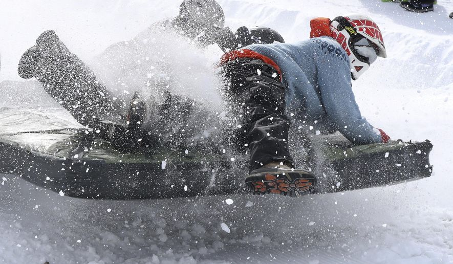 "Adam Armington of Lovell, Maine, right, holds on as his team goes airborne as they cross the finish line during The Mattress Race at the Shawnee Peak ski area, Saturday, March 11, 2017, in Bridgton, Maine. The annual late-season event had a theme of ""a tropical vacation,"" but racers had to deal with mid-winter conditions and a wind chill factor of well below zero degrees F. (AP Photo/Robert F. Bukaty)"
