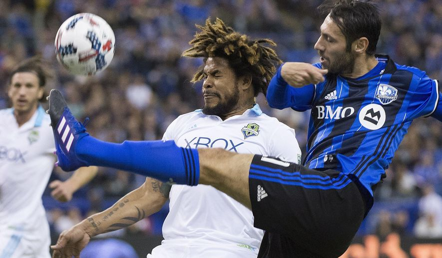Montreal Impact's Matteo Mancosu, right, challenges Seattle Sounders Roman Torres during the first half of a MLS soccer game, Saturday, March 11, 2017 in Montreal. (Graham Hughes/The Canadian Press via AP)