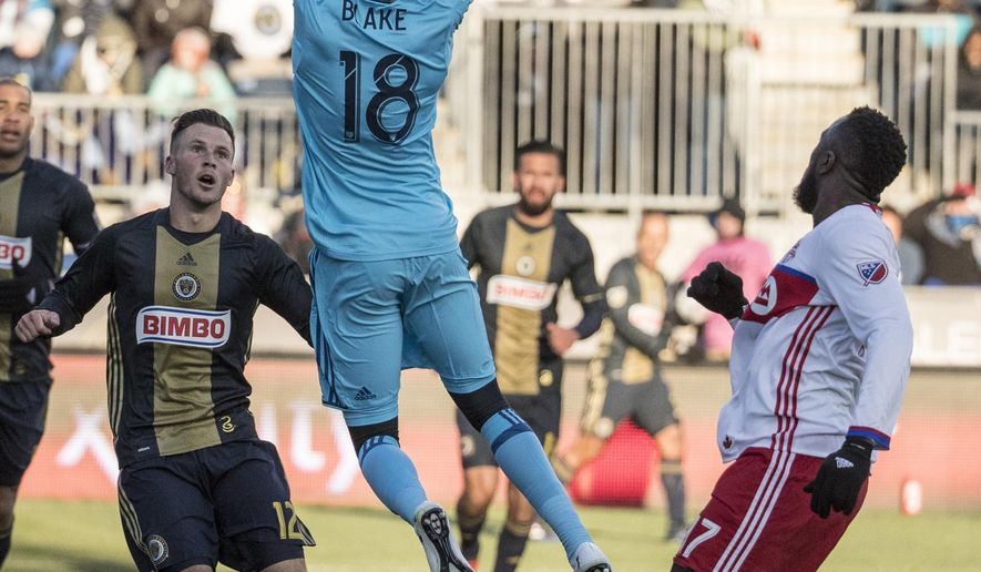 Philadelphia Union's Andre Blake, center, leaps to catch the ball with Keegan Rosenberry, left, and Toronto FC's Jozy Altidore, right, watching during the first half of an MLS soccer match, Saturday, March 11, 2017, in Chester, Pa. (AP Photo/Chris Szagola)