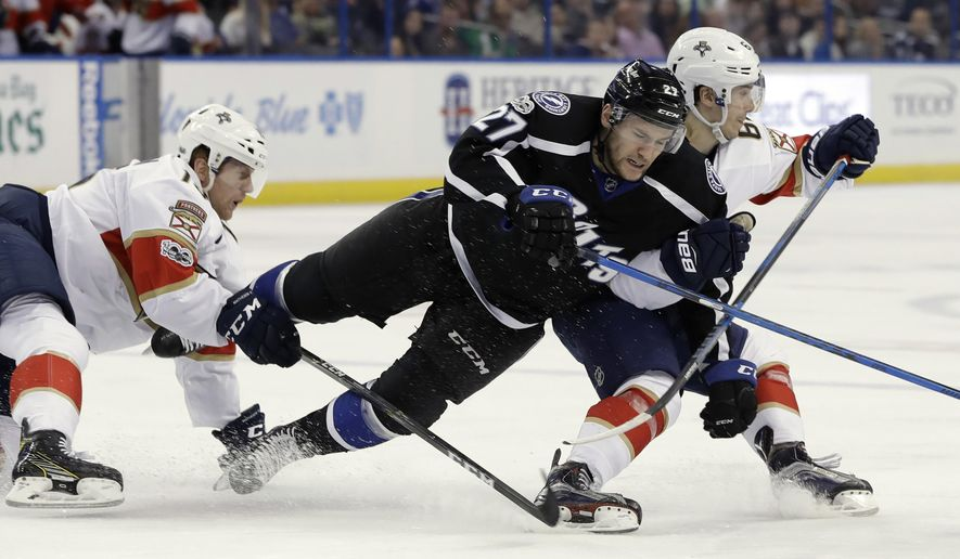 Tampa Bay Lightning left wing Jonathan Drouin (27) is taken down by Florida Panthers defenseman Mark Pysyk (13) and center Denis Malgin (62) during the second period of an NHL hockey game, Saturday, March 11, 2017, in Tampa, Fla. (AP Photo/Chris O'Meara)