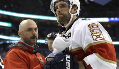 Florida Panthers defenseman Aaron Ekblad is looked at by a trainer after getting checked into the boards by Tampa Bay Lightning center Gabriel Dumont during the second period of an NHL hockey game, Saturday, March 11, 2017, in Tampa, Fla. (AP Photo/Chris O'Meara)