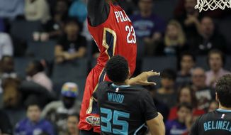 New Orleans Pelicans' Anthony Davis (23) grabs an alley-oop pass and prepares to dunk over Charlotte Hornets' Christian Wood (35) during the first half of an NBA basketball game in Charlotte, N.C., Saturday, March 11, 2017. (AP Photo/Bob Leverone)