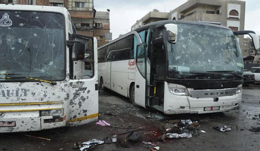 This photo released by the Syrian official news agency SANA shows blood soaked streets and several damaged buses in a parking lot at the site of an attack by twin explosions in Damascus, Syria, Saturday, March 11, 2017. Twin explosions Saturday near religious shrines frequented by Shiite pilgrims in the Syrian capital Damascus killed dozens of people, Arab media and activists report. (SANA via AP)