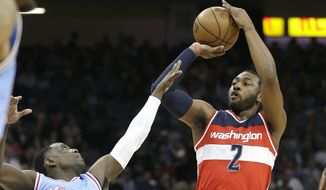 Washington Wizards guard John Wall, right, shots over Sacramento Kings guard Darren Collison during the first half of an NBA basketball game, Friday, March 10, 2017, in Sacramento, Calif. (AP Photo/Rich Pedroncelli)