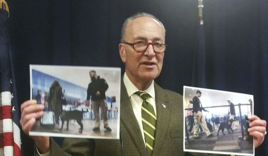 U.S. Sen. Charles Schumer holds up photos of anti-terrorism airport security dogs as he criticizes President Donald Trump Sunday, March 12, 2017, over proposed cuts to the Transportation Security Administration and Coast Guard that the New York Democrat says would put New York at risk, at Schumer's office in New York. The Democrat accused Trump's administration of seeking to slash important funding to free up money to fund a wall at the Mexican border. (AP Photo/Julie Walker)