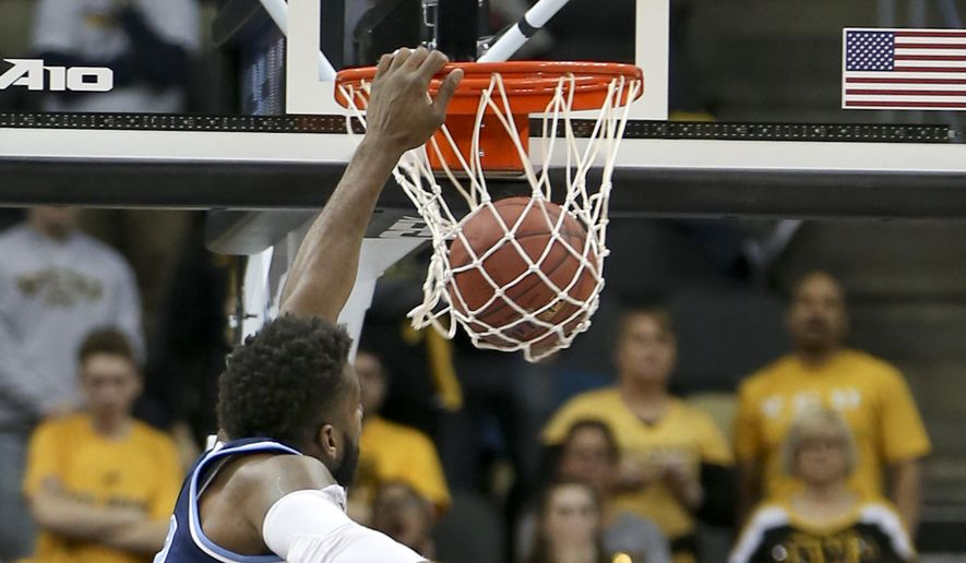 Rhode Island's Hassan Martin, left, dunks over VCU's Ahmed Hamdy-Mohamed (23) during the first half of an NCAA college basketball game in the Atlantic 10 tournament championship, Sunday, March 12, 2017, in Pittsburgh. (AP Photo/Keith Srakocic)