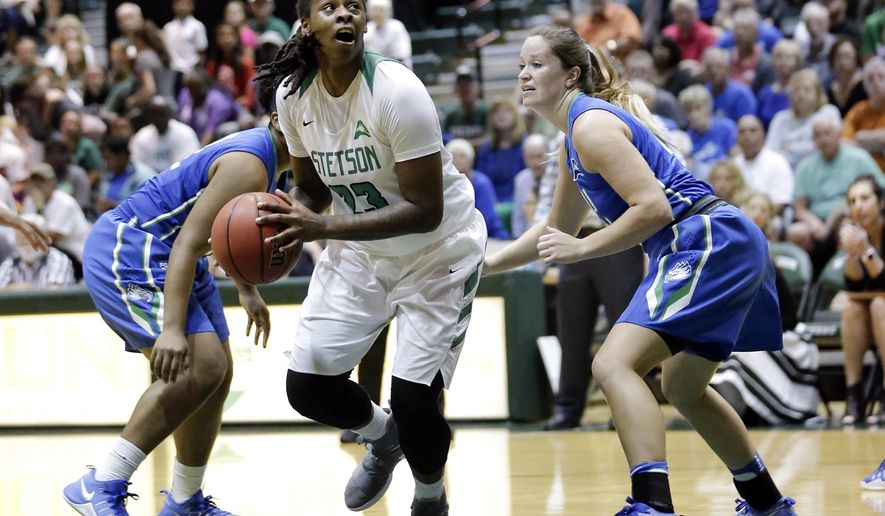 Stetson's Breana Bey, center, looks to take a shot as she gets between Florida Gulf Coast's China Dow, left, and Taylor Gradinjan, right, during the first half of an NCAA Atlantic Sun Conference college championship basketball game, Sunday, March 12, 2017, in DeLand, Fla. (AP Photo/John Raoux)