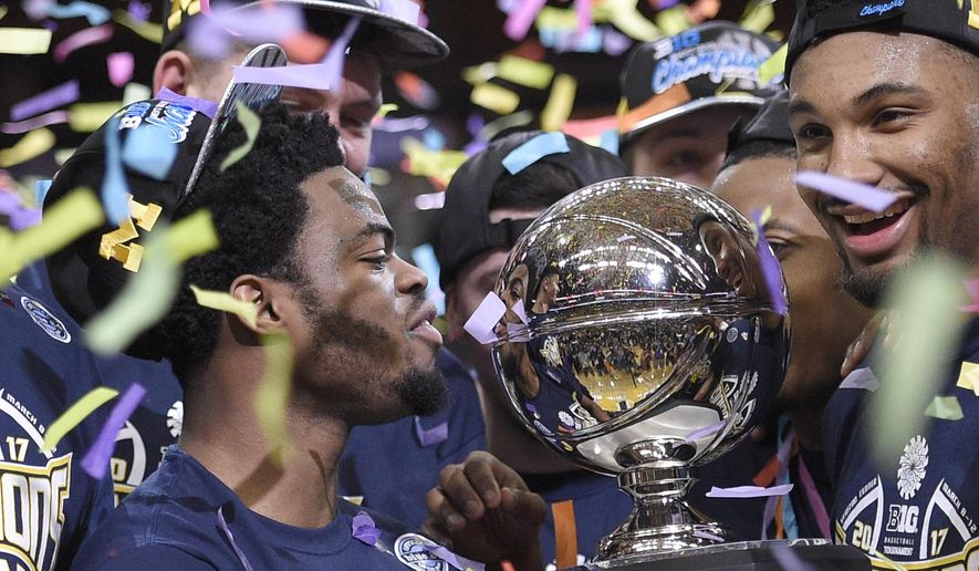 Michigan's Derrick Walton Jr., left, looks at the trophy as he and teammates celebrate after defeating Wisconsin 71-56 in an NCAA college basketball game for the Big Ten tournament title, Sunday, March 12, 2017, in Washington. (AP Photo/Nick Wass) **FILE**