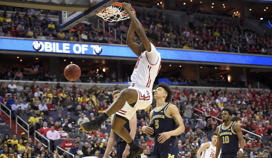 Wisconsin forward Nigel Hayes dunks in front of Michigan forward D.J. Wilson (5) and guard Derrick Walton Jr. (10) during the first half of an NCAA college basketball game for the Big Ten tournament title, Sunday, March 12, 2017, in Washington. (AP Photo/Nick Wass)