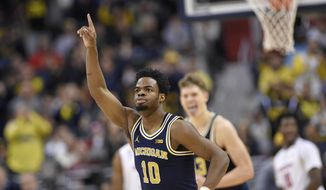 Michigan guard Derrick Walton Jr. (10) reacts after he hit a 3-pointer during the first half of the Big Ten NCAA college basketball championship game against Wisconsin, Sunday, March 12, 2017, in Washington. (AP Photo/Nick Wass)