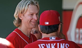 Cincinnati Reds starting pitcher Bronson Arroyo, left, smiles as he talks with pitching coach Mack Jenkins after Arroyo pitched two scoreless innings of a spring training baseball game against the Milwaukee Brewers, Sunday, March 12, 2017, in Goodyear, Ariz. (AP Photo/Ross D. Franklin)