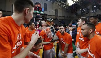 Princeton's Steven Cook, center, kisses the Ivy League Basketball Tournament Trophy while surrounded by teammates following an NCAA college basketball championship game in the Ivy League Tournament against Yale, Sunday, March 12, 2017, in Philadelphia. (AP Photo/Chris Szagola)