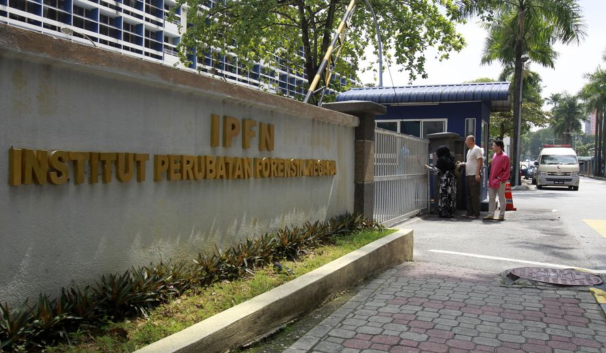 "People make their way to enter the forensic department at Kuala Lumpur Hospital in Kuala Lumpur, Malaysia on Sunday, March 12, 2017.  Malaysia's Foreign Minister Anifah Aman said the government hopes to begin formal talks with North Korea in the ""next few days"" on solving a diplomatic dispute that has seen the two countries bar each other's citizens from leaving. The dispute stems from the mysterious poisoning death of the estranged half brother of North Korean leader Kim Jong Un on Feb. 13 at Kuala Lumpur's airport. (AP Photo/Daniel Chan)"