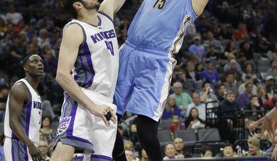 Denver Nuggets forward Nikola Jokic, right, shoots over Sacramento Kings center Kosta Koufos during the first half of an NBA basketball game, Saturday, March 11, 2017, in Sacramento, Calif. (AP Photo/Rich Pedroncelli)