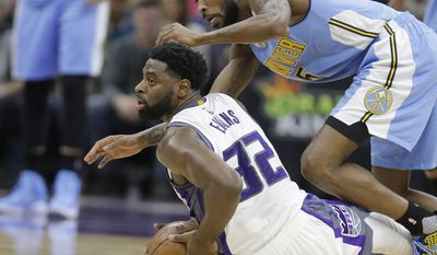 Sacramento Kings guard Tyreke Evans, left, looks to pass after coming up with a loose ball against Denver Nuggets guard Will Barton during the first half of an NBA basketball game, Saturday, March 11, 2017, in Sacramento, Calif. (AP Photo/Rich Pedroncelli)