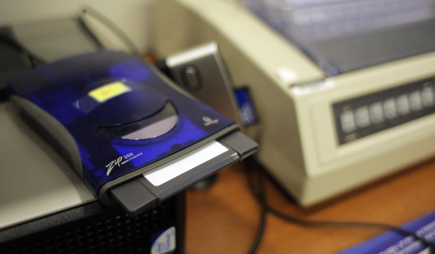 In this Thursday, March 9, 2017 photo, a zip disk drive and dot matrix printer sit at the Bexar County Elections office in San Antonio. Bexar County's voting equipment is among the oldest in America's second-largest state and will have to be replaced soon. But money to do so is scarce, and that scenario is playing out around the country. (AP Photo/Eric Gay)