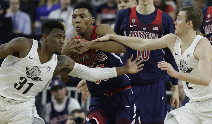 Arizona's Allonzo Trier, center, competes for the ball with Oregon's Dylan Ennis, left, and Casey Benson during the first half of an NCAA college basketball game for the championship of the Pac-12 men's tournament Saturday, March 11, 2017, in Las Vegas. (AP Photo/John Locher)