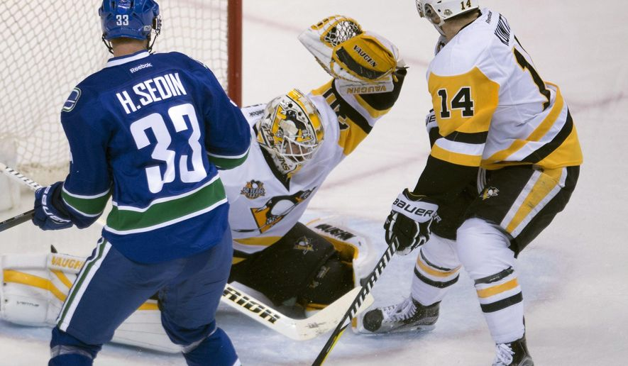 Pittsburgh Penguins goalie Matt Murray (30) stops a shot from Vancouver Canucks center Henrik Sedin (33) as Penguins left wing Chris Kunitz (14) watches during the third period of an NHL hockey game Saturday, March 11, 2017, in Vancouver, British Columbia. (Jonathan Hayward/The Canadian Press via AP)